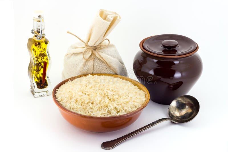 La composición de las avenas mondadas del arroz Steamed en una arcilla pial al lado de un pote de arcilla y de una cuchara de cob fotografía de archivo libre de regalías