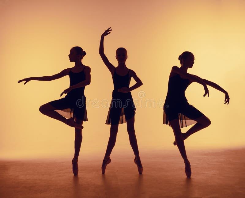 La composición de las siluetas de tres bailarines jovenes en ballet presenta en un fondo anaranjado imagen de archivo