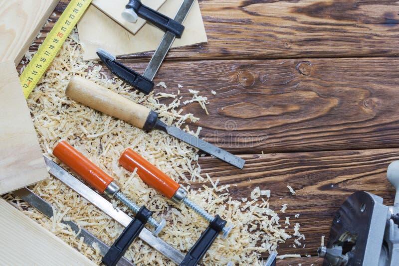 La composición de los clips, de los cinceles, y de los microprocesadores en la mesa en el taller de madera imagenes de archivo
