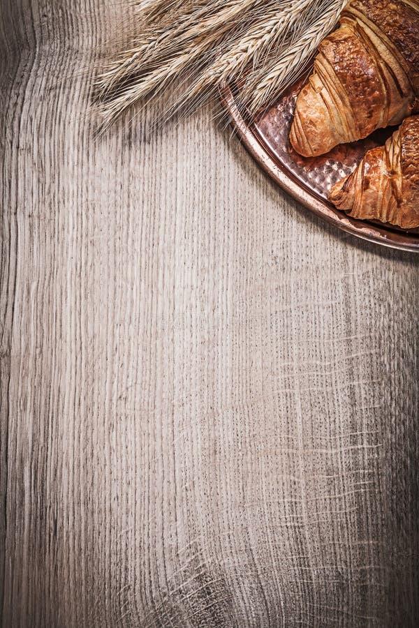 La composición de los oídos del centeno del trigo rueda la bandeja de cobre amarillo en el tablero de madera foto de archivo