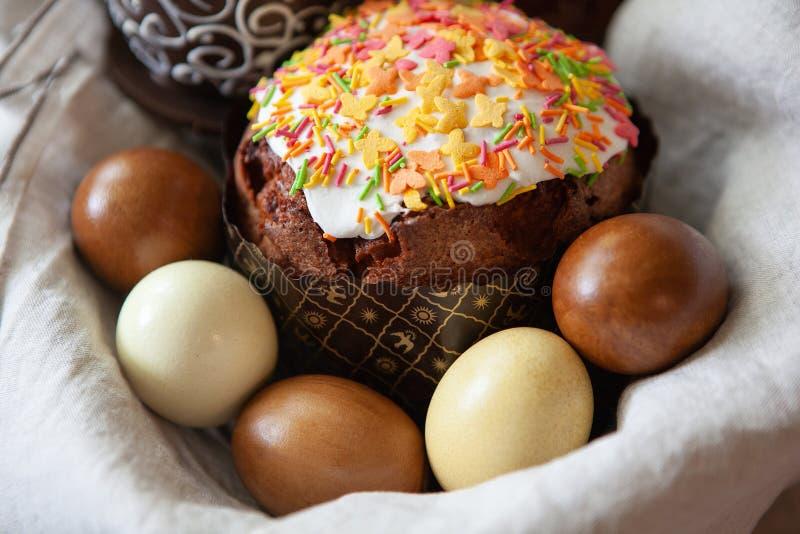 La composición de Pascua con la torta apetitosa, maravillosamente adornada de Pascua, teñió los huevos en una cesta en la tela de foto de archivo libre de regalías