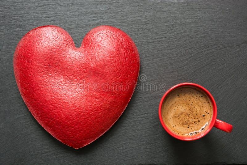 La composición del día de tarjetas del día de San Valentín con la taza de café roja y el corazón grande del terciopelo rojo se ap fotos de archivo libres de regalías