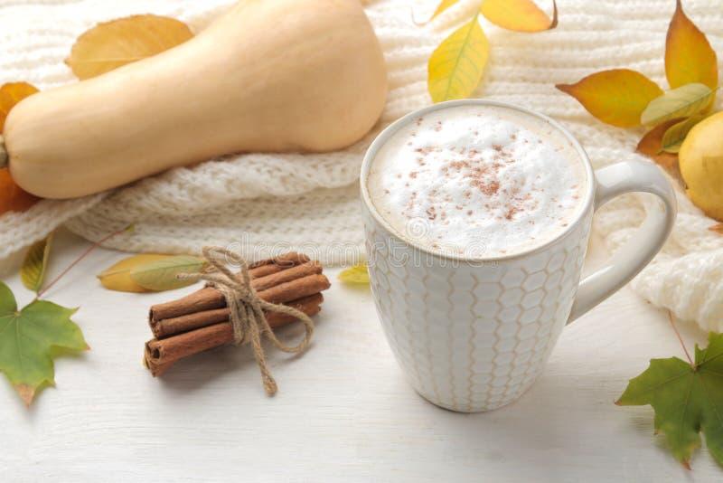 La composición del otoño con café caliente, una bufanda caliente y amarillo se va en una tabla de madera blanca imágenes de archivo libres de regalías