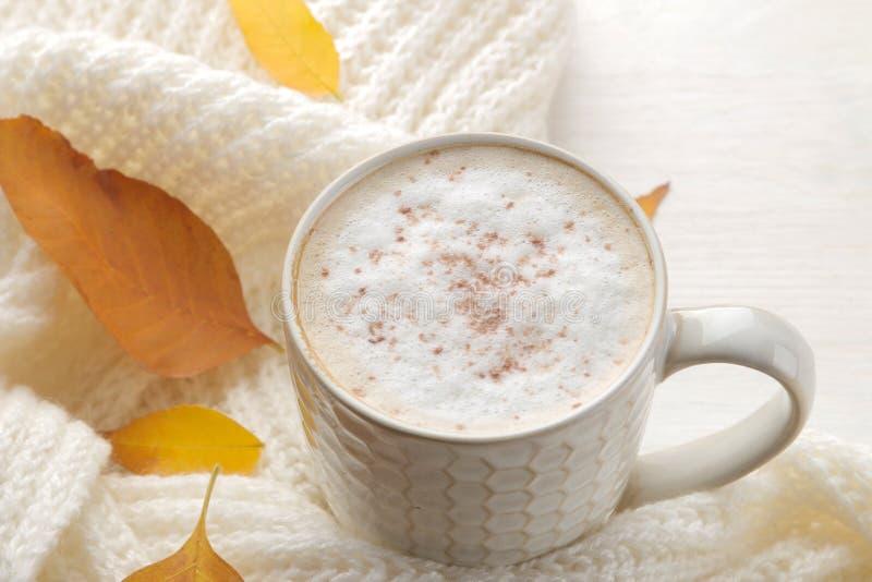 La composición del otoño con café caliente, una bufanda caliente y amarillo se va en una tabla de madera blanca foto de archivo libre de regalías
