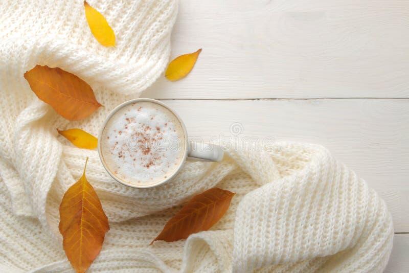 La composición del otoño con café caliente, una bufanda caliente y amarillo se va en una tabla de madera blanca visión superior c foto de archivo libre de regalías