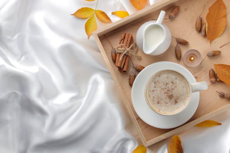 La composición del otoño con café caliente y amarillo se va en una bandeja en la cama Visión desde arriba imagenes de archivo