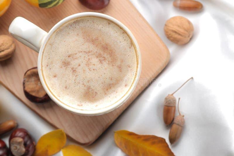 La composición del otoño con café caliente y amarillo se va en una bandeja en la cama Visión desde arriba foto de archivo libre de regalías