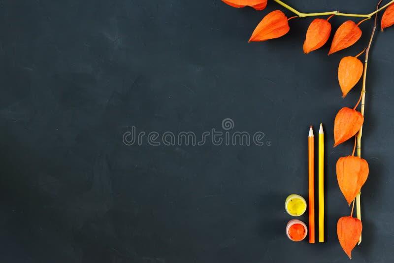 La composición del otoño con el papel del arte, acuarelas, color dibujó a lápiz en el tablero de tiza, physalis anaranjado adorna imagen de archivo libre de regalías