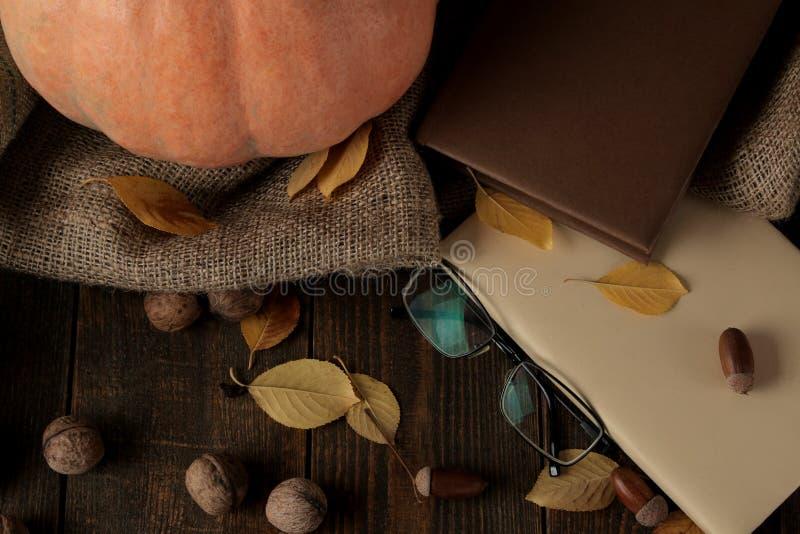 La composición del otoño con una calabaza y los libros y amarillo se va en una tabla marrón fotos de archivo