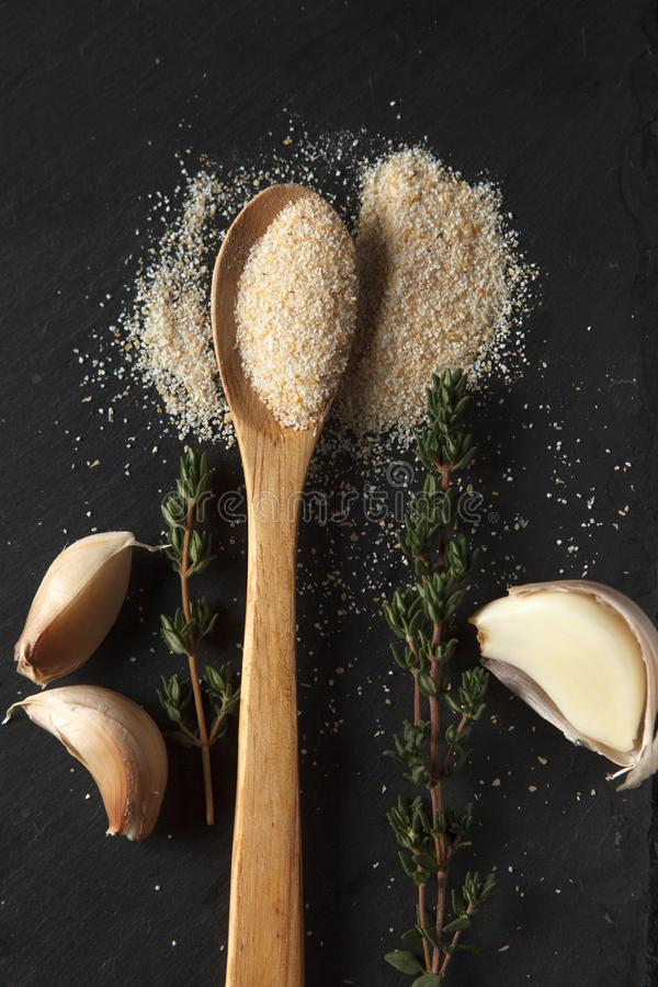 La composición del polvo del ajo, las puntillas del tomillo y los clavos en pizarra negra suben fotos de archivo libres de regalías
