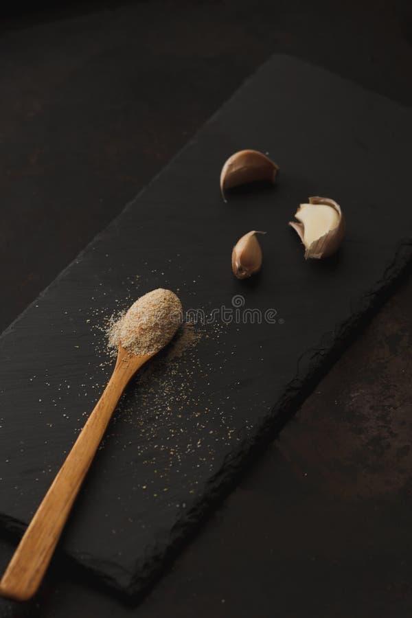 La composición del polvo del ajo y los clavos en pizarra negra suben foto de archivo