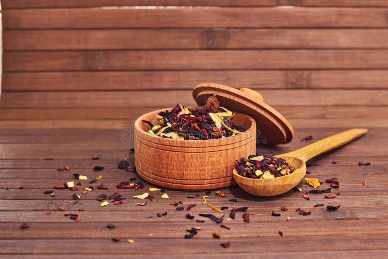 La composición del té natural con las hojas de subió Foto macra de los pétalos del té en un tablero de madera El té con los pétal fotografía de archivo
