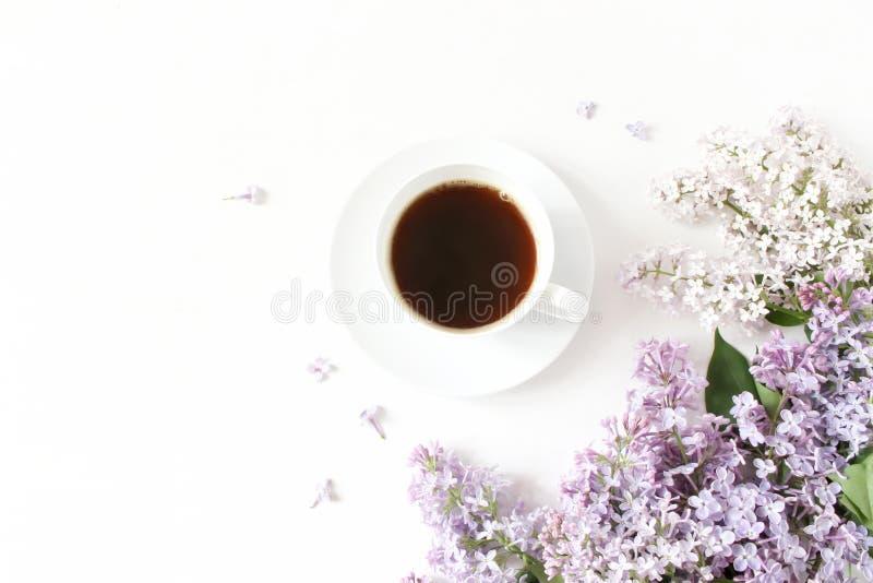 La composición floral hecha de la lila púrpura hermosa, syringa florece en el fondo de madera blanco con la taza de café foto de archivo