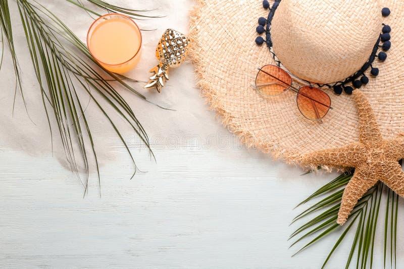 La composición plana de la endecha con el sombrero y la playa elegantes se opone imagenes de archivo
