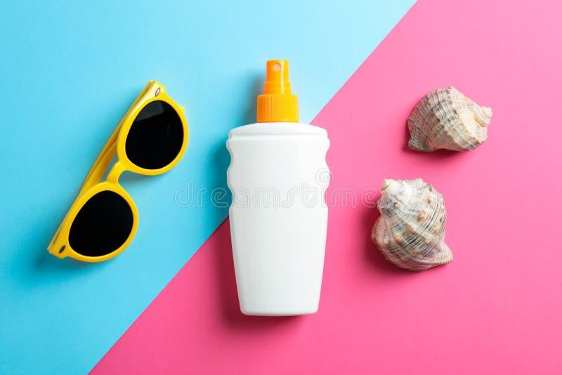 La composición puesta plana con las gafas de sol, protección solar ruega y concha marina en el fondo de dos tonos, visión superio imagen de archivo