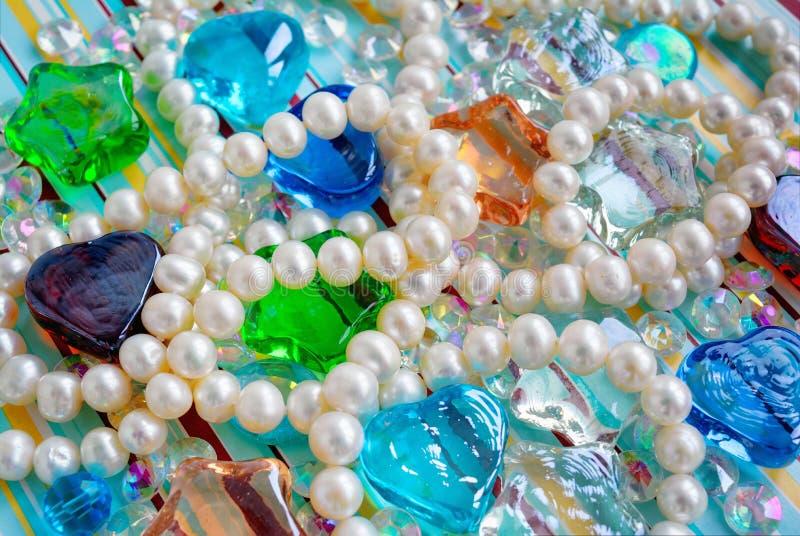 La composition abstraite avec le collier pâle naturel de perles de perle, a souillé la forme d'étoile en verre et de coeur images stock