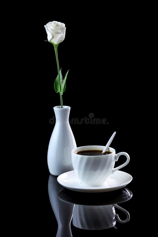 La composition avec la tasse de café et la rose de blanc sur un noir se reflètent photo libre de droits
