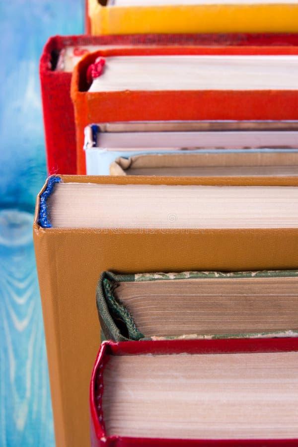 La composition avec livre cartonné coloré de vieux vintage réserve l'empilement, le journal intime sur la table en bois de plate- photographie stock