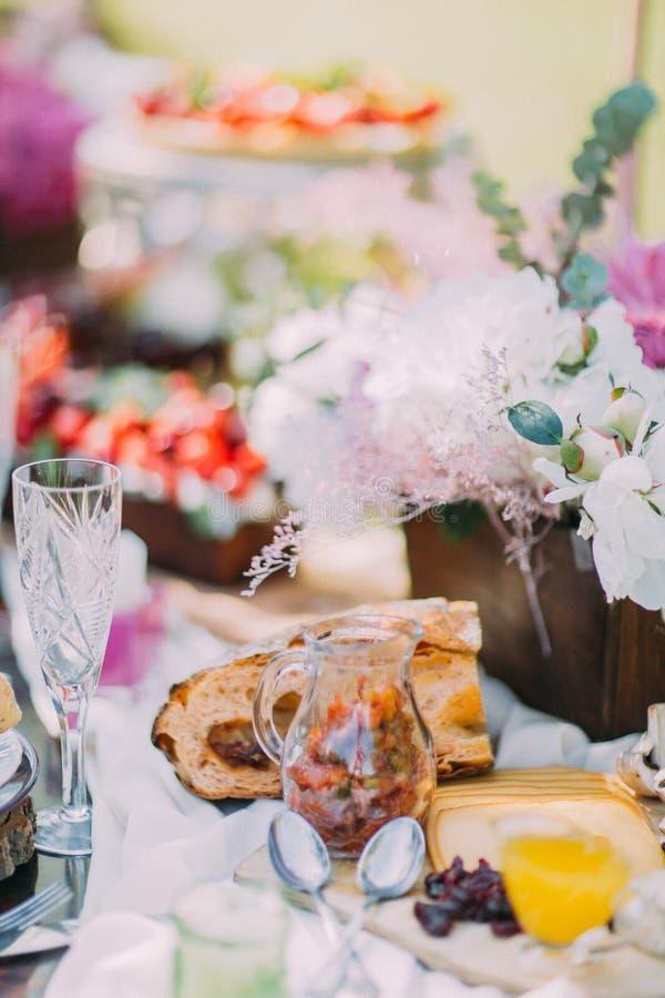 La composition de l'arrangement de table de mariage La table est pleine de belles fleurs dans le pot en bois, fromage savoureux images libres de droits