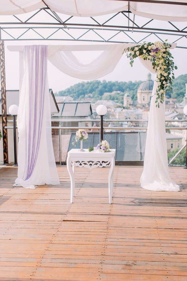 La composition de mariage de la petites table et voûte blanches décorées des fleurs colorées images libres de droits