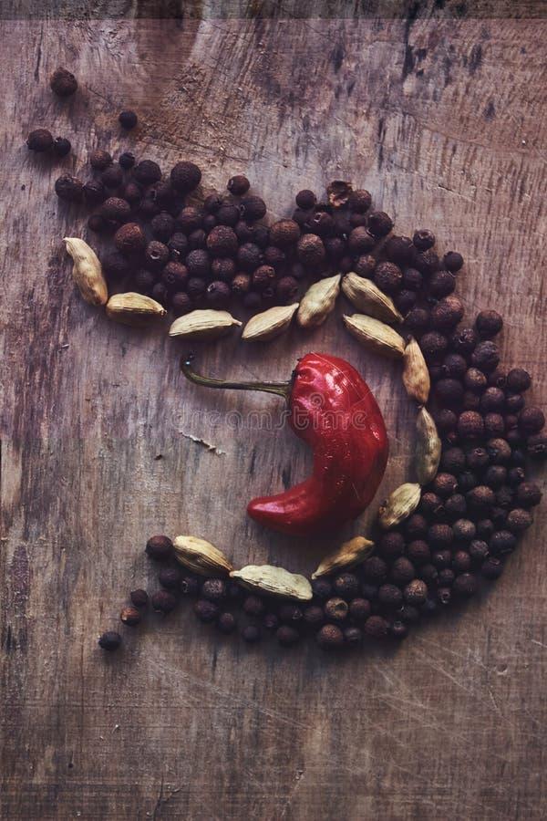 La composition des fruits du poivre noir, des haricots et d'un poivron rouge au milieu photo libre de droits