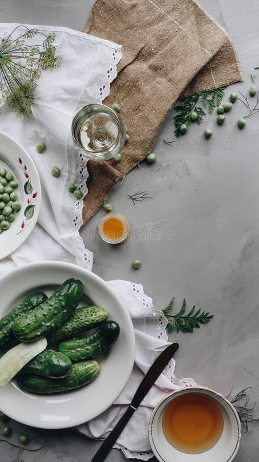 La composition rustique du petit déjeuner, les légumes verts, la tasse de thé et les beaux tissus décorent la table photographie stock libre de droits