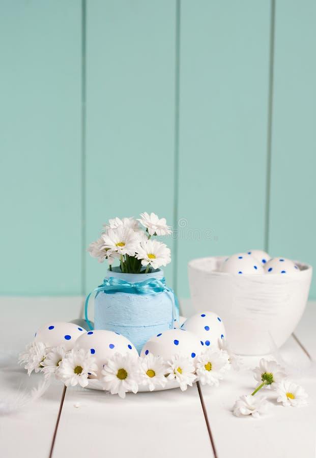 La composition se compose des oeufs de pâques et des fleurs de ressort images stock