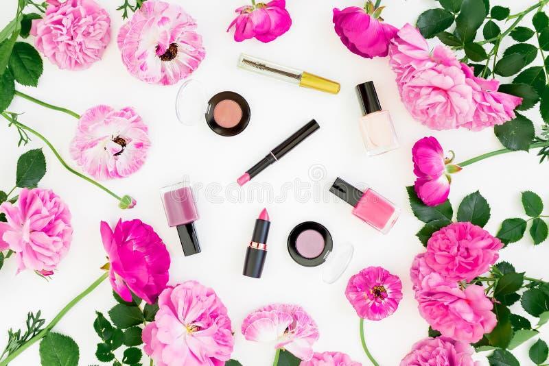 La composizione in bellezza con il rosa fiorisce il mazzo e compone i cosmetici su fondo bianco Vista superiore Scrittorio femmin fotografia stock