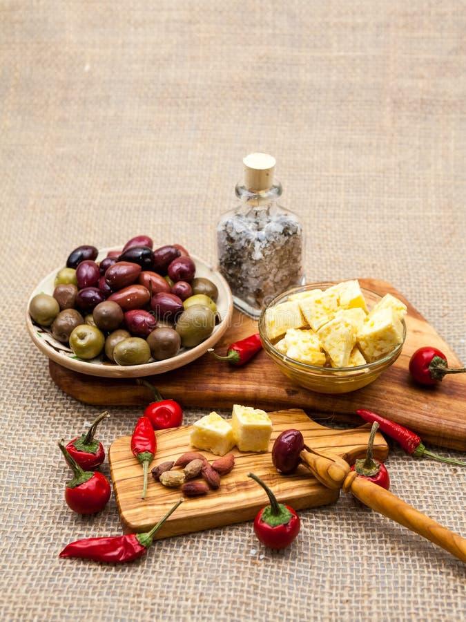 La composizione con formaggio collega in olio d'oliva, olive e peperoncini fotografia stock libera da diritti