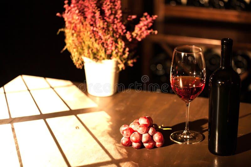 La composizione della bottiglia, del bicchiere di vino e del mazzo di uva disposta vicino al vaso di fiore sulla tavola nello scu fotografia stock