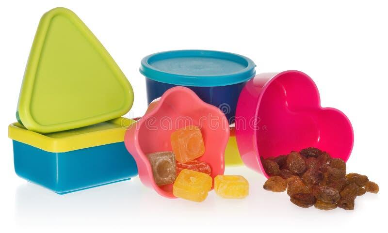La composizione delle scatole colorate e delle muffe chiuse di caramella ed uva passa fotografie stock