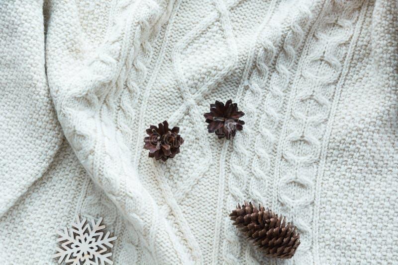 La composizione in Natale con il cono, fiocchi di neve su bianco ha tricottato il maglione Scheda di festa Stile dell'annata Disp immagini stock