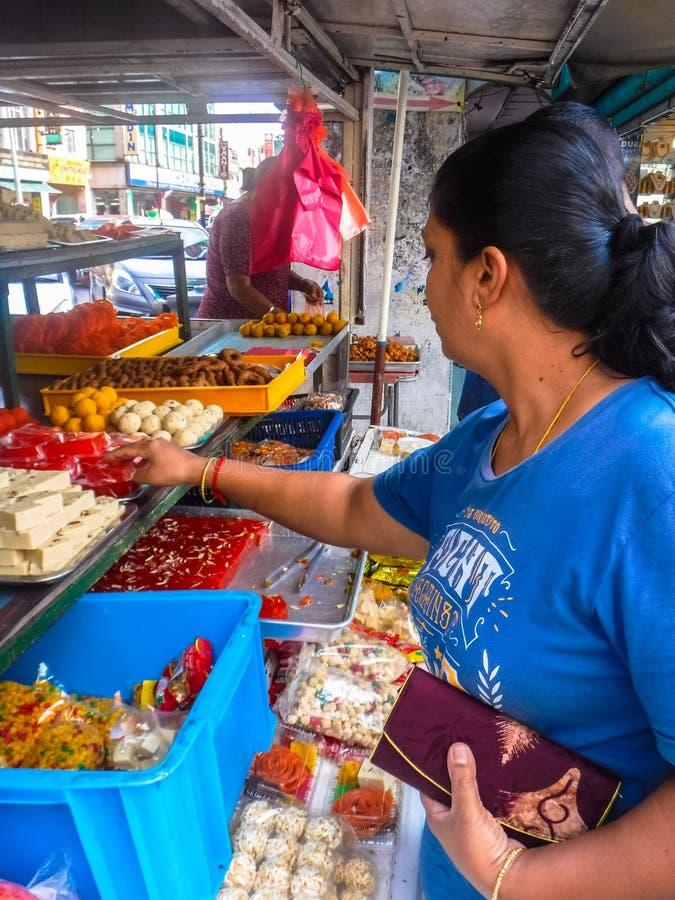 La compra de la mujer clasificó los dulces indios en poca ciudad de la India imagen de archivo libre de regalías