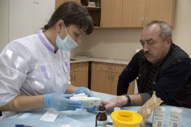 La comprobación de la enfermera sirve el nivel de azúcar de sangre fotos de archivo