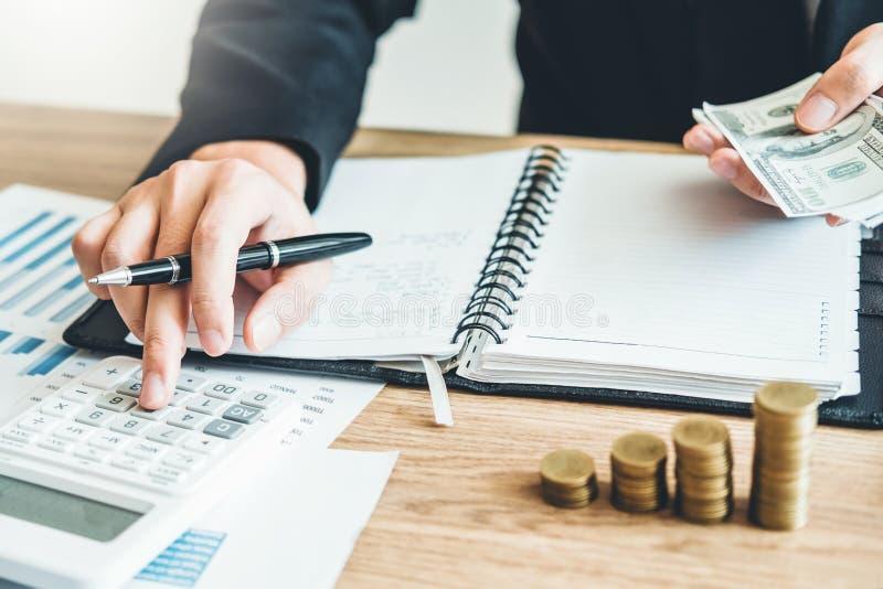 La comptabilité d'homme d'affaires calculant le budget économique coûté mettant la rangée et la pièce de monnaie écrivent le conc photo libre de droits