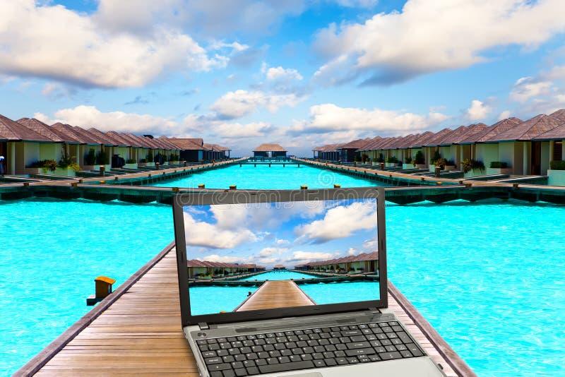La computadora portátil en una playa