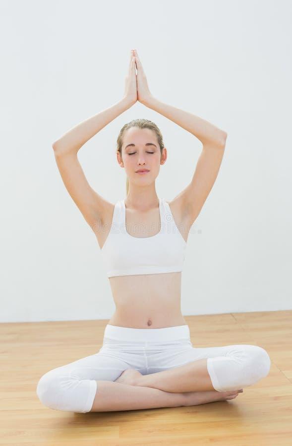 La concentrazione della donna calma che medita la seduta nella posizione di loto con le mani si è alzata nella preghiera fotografia stock libera da diritti