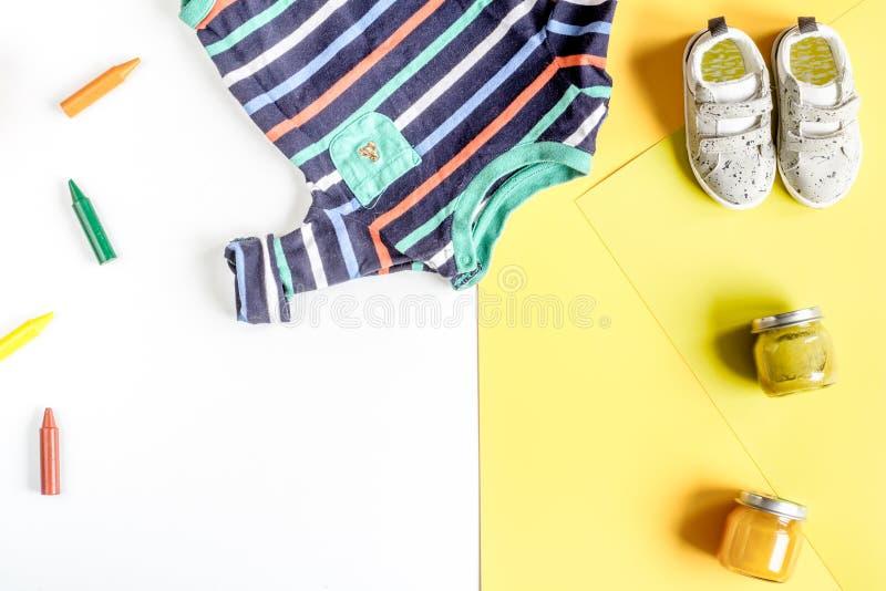 La conception de bureau d'enfants avec des jouets et les vêtements jaunissent la maquette blanche de vue supérieure de fond photos stock