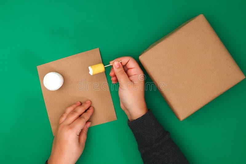La conception originale d'un cadeau de Noël de papier de métier, peinture blanche, un timbre des pommes de terre Point par point  photographie stock libre de droits