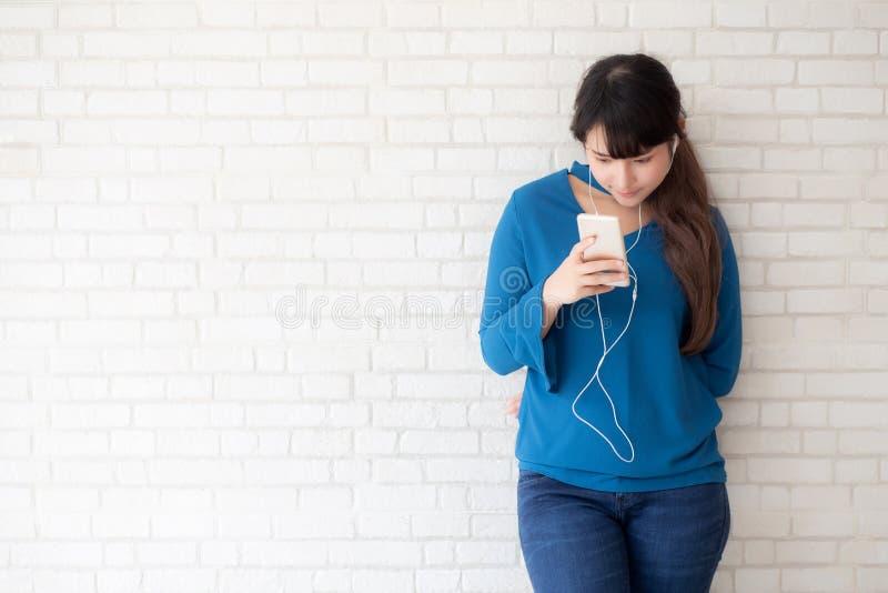 La condizione asiatica della giovane donna del bello ritratto felice gode di ed il divertimento ascolta musica con la cuffia sul  fotografia stock
