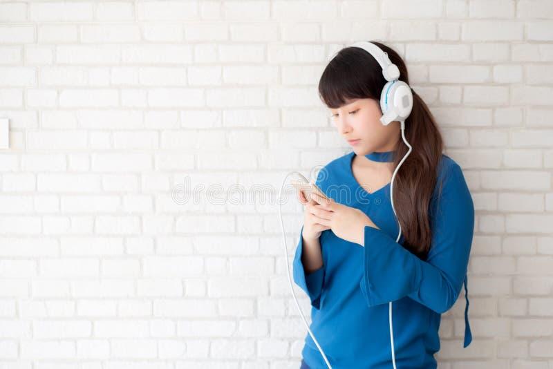 La condizione asiatica della giovane donna del bello ritratto felice gode di ed il divertimento ascolta musica con la cuffia sul  immagini stock libere da diritti