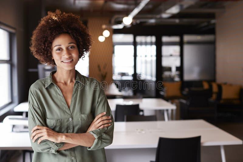 La condizione creativa femminile nera millenaria in un ufficio open space con le armi ha attraversato sorridere alla macchina fot immagine stock