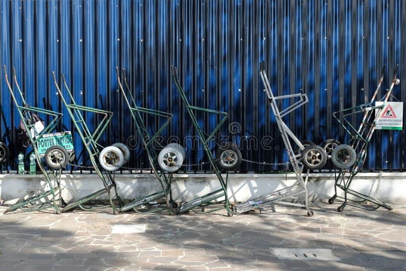 La condizione dei carretti della mano di Parters accanto ad un blu scuro recinta Venezia, Italia fotografie stock libere da diritti