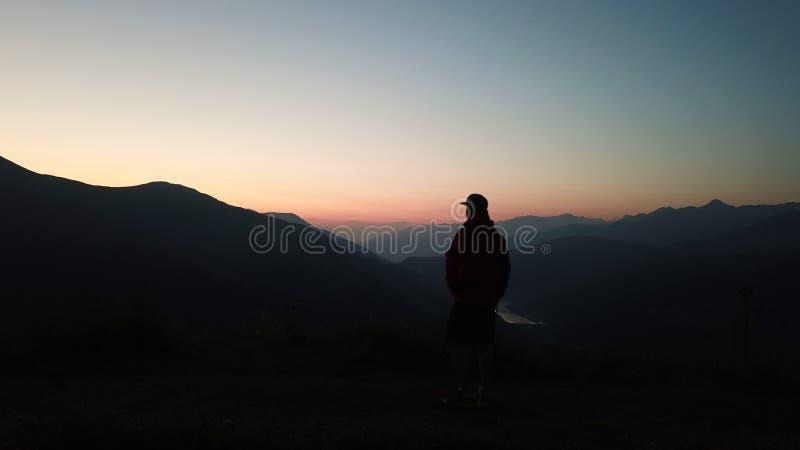 La condizione di rilassamento dell'uomo del viaggiatore e godere delle montagne serene di vista abbelliscono all'alba immagine stock