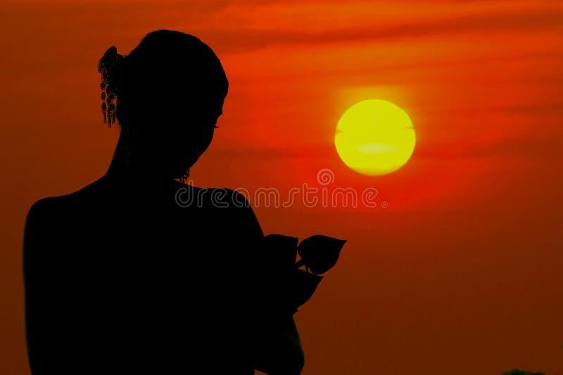 La condizione nera della donna della siluetta che abbraccia un tramonto del fiore di loto fotografia stock
