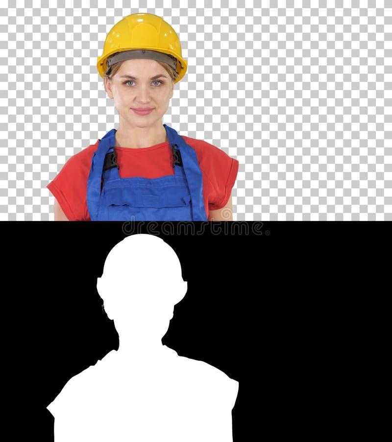 La condizione sorridente della donna del lavoratore del costruttore e le pose cambianti piegano le mani, le mani sulle anche, man fotografia stock libera da diritti