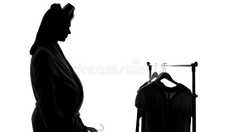 La condizione triste della donna incinta vicino al guardaroba, manca i vestiti favoriti, la depressione fotografie stock libere da diritti