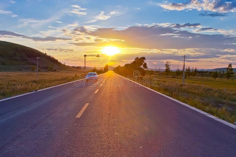La conducción de automóviles en puesta del sol fotografía de archivo libre de regalías