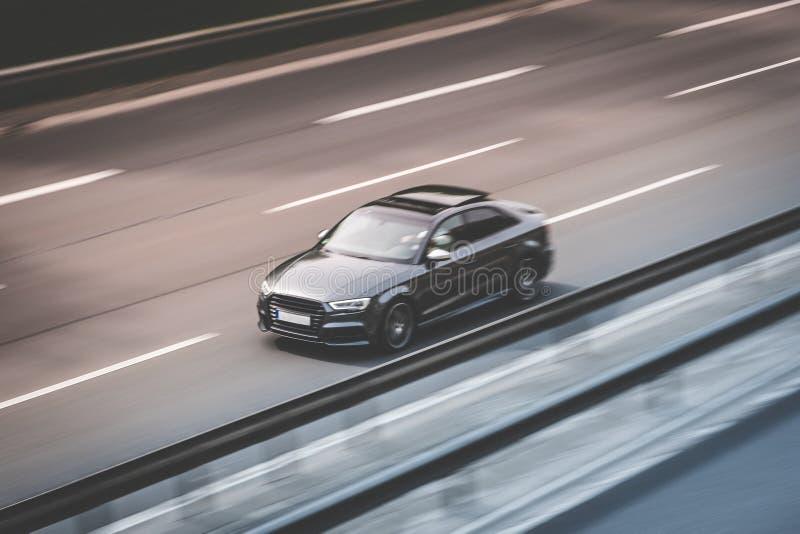 La conduite noire jeûnent sur la route de route, tache floue de mouvement photographie stock
