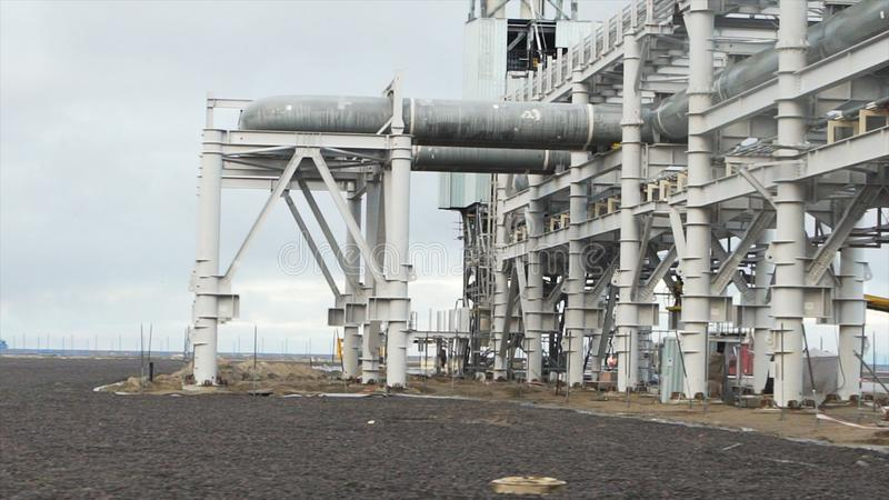 La conduttura industriale ha costruito vicino alla spiaggia Grande raffineria di petrolio vicino al mare in una mattina nuvolosa  immagini stock libere da diritti